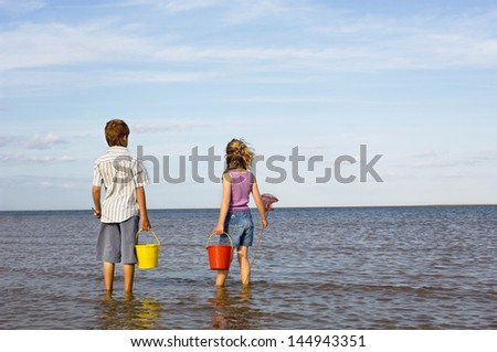 Rear view of a brother and sister with buckets and small fishnet enjoying the sea view - stock photo