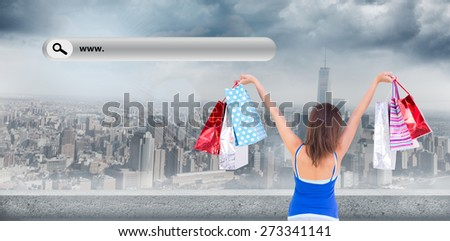 Rear view of a brunette woman raising shopping bags against large city - stock photo