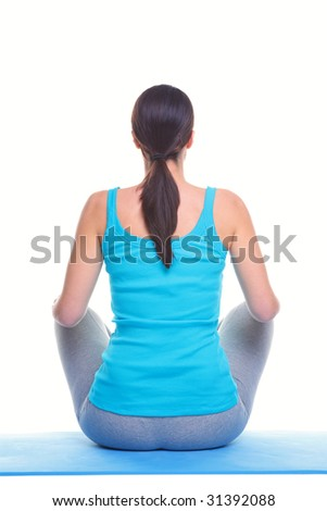Rear view of a brunette woman sitting on a yoga mat, isolated on a white background. - stock photo