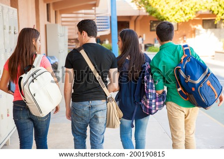Rear view of a bunch of high school students walking down the hallway - stock photo
