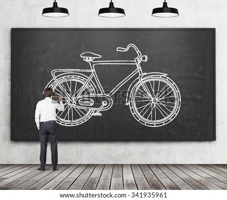 Rear view of a businessman in formal clothes who is drawing a sketch of a bicycle on the huge black chalkboard. A concept of environmental friendly ways of commuting or travelling. - stock photo