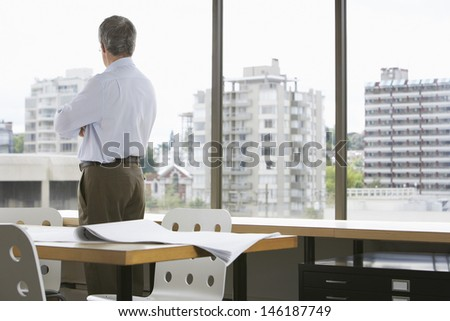 Rear view of a businessman looking out of office window - stock photo