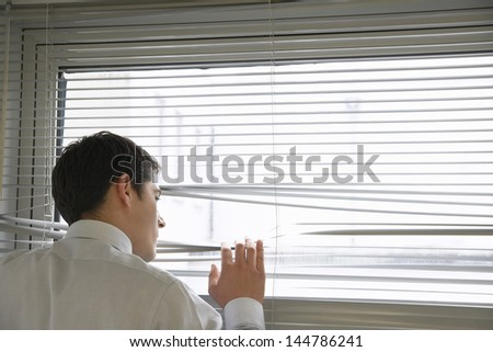Rear view of a businessman looking out of the office window through blinds - stock photo