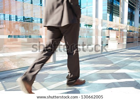 Rear view of a businessman low section walking fast by a modern office building in the financial district city, outdoors. - stock photo