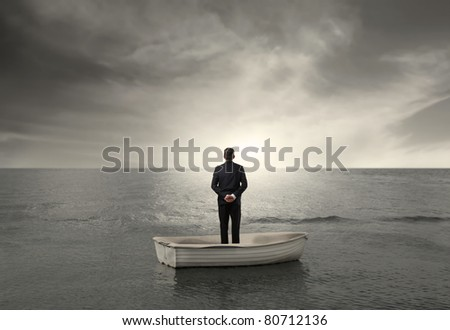 Rear view of a businessman on a boat in the sea - stock photo
