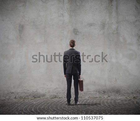 Rear view of a businessman standing in front of a wall - stock photo