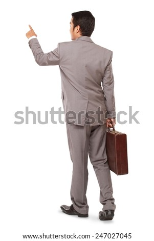 Rear view of a businessman standing pointing and holding a briefcase, isolated on white background
