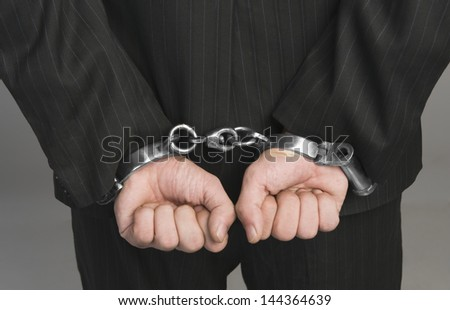 Rear view of a businessman tied up with handcuffs - stock photo