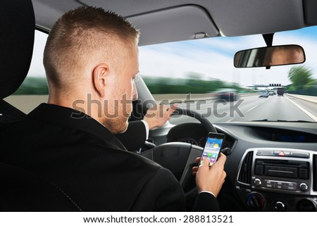 Rear View Of A Businessman Using Cellphone While Driving Car - stock photo