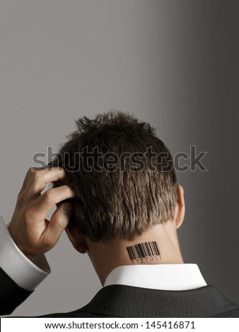Rear view of a businessman with barcode tattoo on neck scratching his head against gray background - stock photo