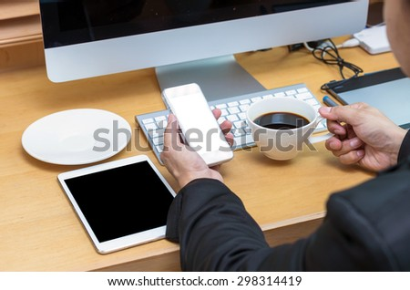 Rear view of a businessman working with a computer and tablet when drinking the coffee at office desk - stock photo