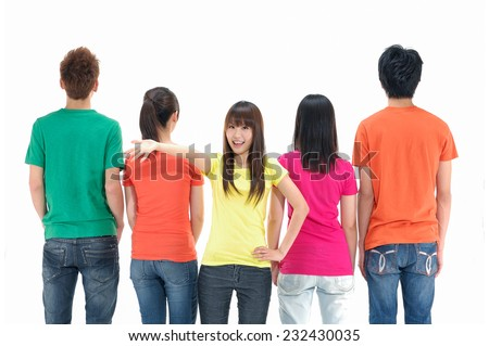 Rear view of a casual group of people with a woman facing the camera - stock photo