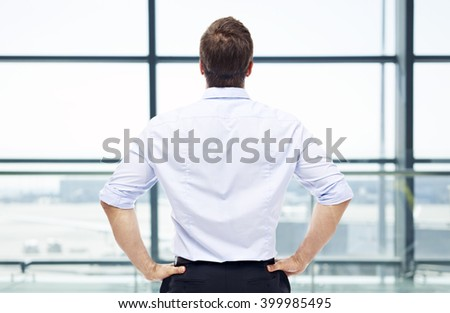 rear view of a caucasian man standing by the window looking out and thinking in a modern airport. - stock photo
