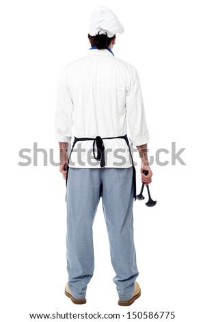 Rear view of a chef holding utensils - stock photo