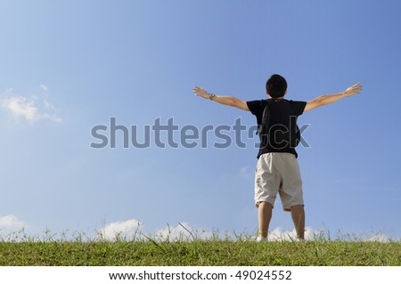 Rear view of a college student with his arms raised while standing outdoors - stock photo