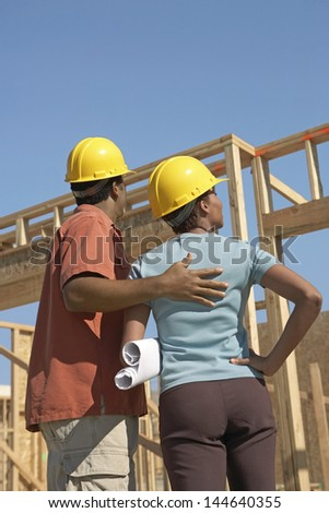 Rear view of a couple in hardhats with blueprints at building site