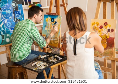 Rear view of a couple of young adults working on their own paintings while studying at an art school - stock photo