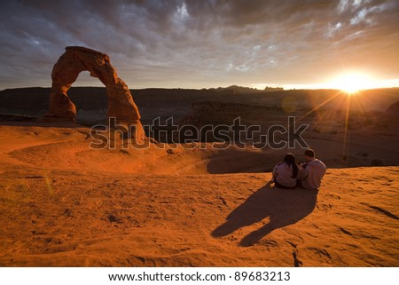 Rear view of a couple sitting at the Delicate Arch in Arches National park at sunset - stock photo