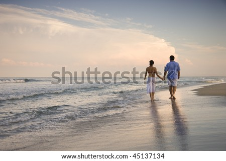 Rear view of a couple walking on the beach, holding hands. Horizontal shot.