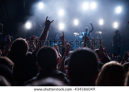 Rear view of a crowd at a festival with their hands raised in the air.