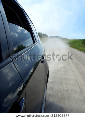 Rear view of a dusty road from a car window, speed concept