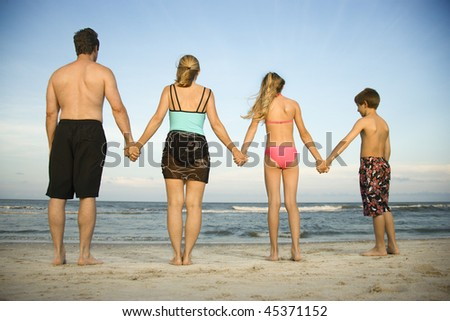 Rear view of a family holding hands at the beach. Horizontal shot. - stock photo
