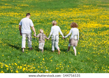 rear view of a family walking on flower meadow