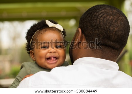 Rear view of a father holding his smiling daughter.