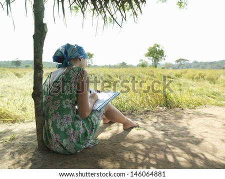 Rear view of a female tourist in dress sitting under hut roof in field - stock photo