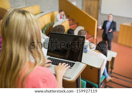 Rear view of a female using laptop with students and teacher at the college lecture hall - stock photo