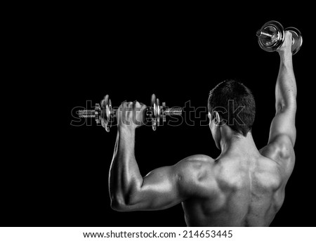 Rear view of a fitness man lifting weights on black background - stock photo