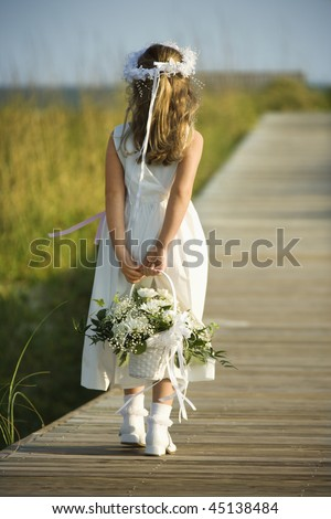 Rear view of a flower girl walking on a boardwalk holding a flower basket behind her back. Vertical shot. - stock photo