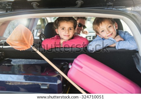 Rear view of a four people family in their car leaving for the holidays. The smiling little girl and boy are turned on their seat, looking at camera. A net and a pink suitcase are in the trunk