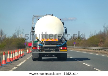 Rear view of a fuel tanker driving along a dual carriageway - stock photo