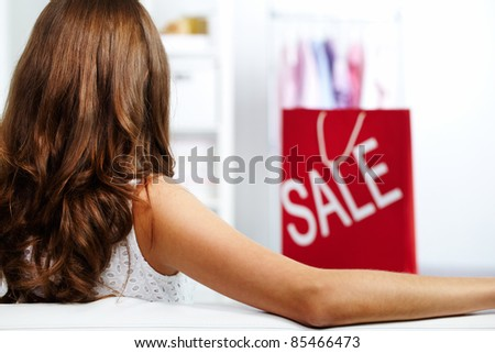 Rear view of a girl sitting at shop at sale period - stock photo