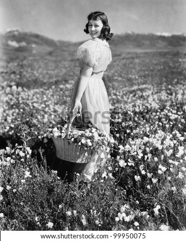 Rear view of a girl standing in a meadow holding a flower basket and smiling - stock photo