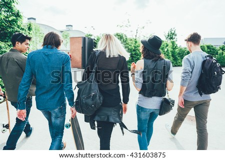Rear view of a group of friends walking in the street of the city, holding skateboard and chatting - technology, friendship concept