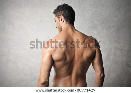 Rear view of a handsome bare-chested man - stock photo