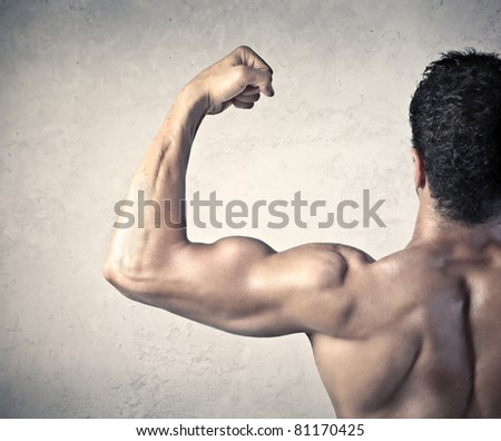 Rear view of a handsome man showing his biceps - stock photo