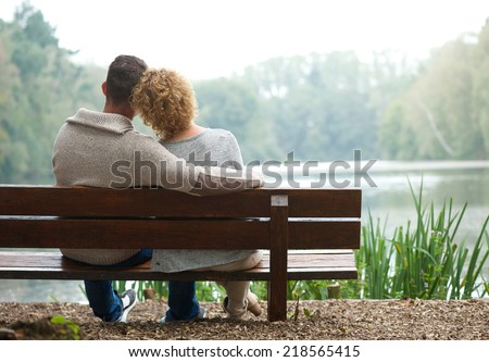 Rear view of a happy couple sitting together on bench outdoors - stock photo