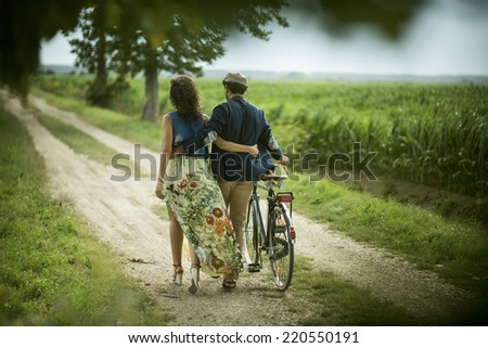 Rear view of a happy couple walking holding bike - stock photo