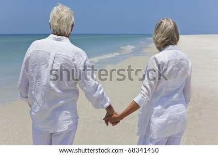 Rear view of a happy senior man and woman couple together holding hands and looking out to sea on a deserted tropical beach with bright clear blue sky - stock photo