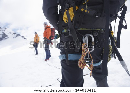 Rear view of a hiker with backpack and safety rope while two friends ahead on snowy landscape - stock photo