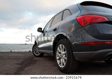 Rear view of a luxury SUV parked near the sea - stock photo