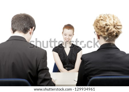 Rear view of a male and female personnel officer interviewing an attractive smiling female candidate for a vacant job position in a corporation - stock photo