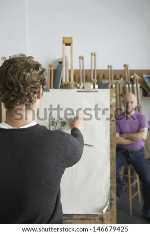 Rear view of a male artist drawing charcoal portrait of model in studio - stock photo