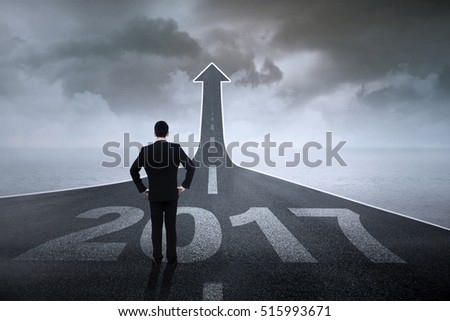 Rear view of a male entrepreneur standing on a road turning into an upward arrow with number 2017