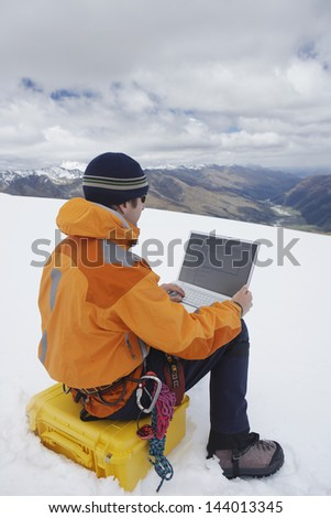 Rear view of a male hiker using laptop on snowy mountain landscape - stock photo