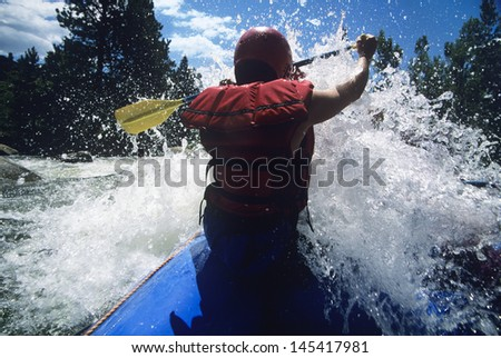 Rear view of a male kayaker paddling through rapids - stock photo