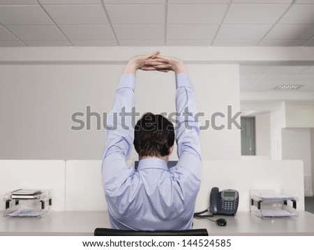 Rear view of a male office worker stretching at desk